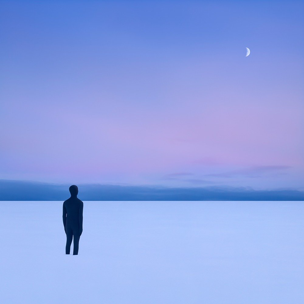 Person in white desert looking at the moon