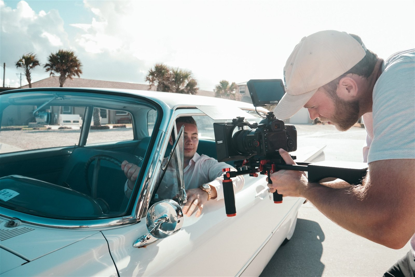 Photographer shooting guy inside a car