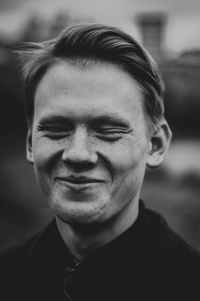 Black and white portrait of guy laughing and eyes closed