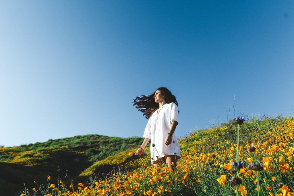 Girl in field with flowers and blue sky