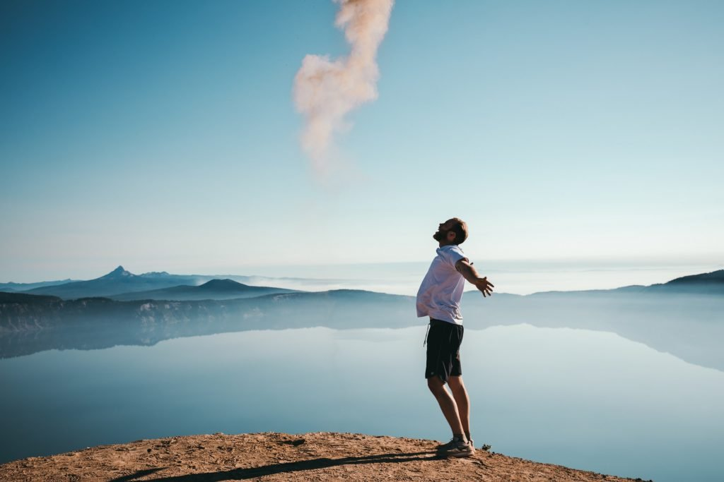 guy shouting with open arms in nature with blue sky and lake