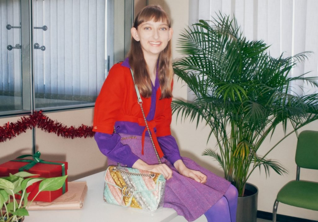 A woman smiling and holding her handbag in the latest 90s holiday campaign from Gucci