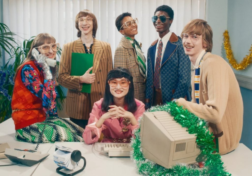 Group of people sitting behind a desk at the 90s holiday campaign from Gucci in the latest 90s holiday campaign from Gucci